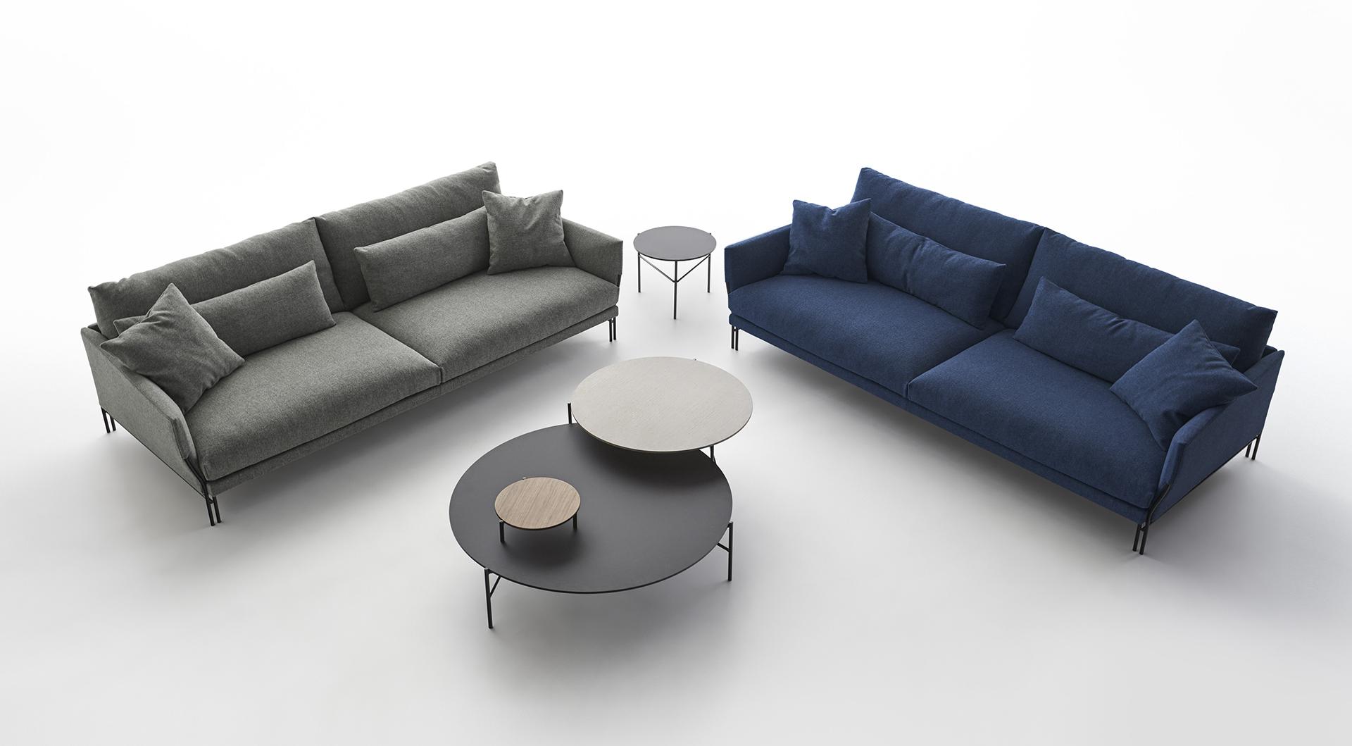 Sofá Majestic de Carmenes en gris y azul con mesas auxiliares redondas.