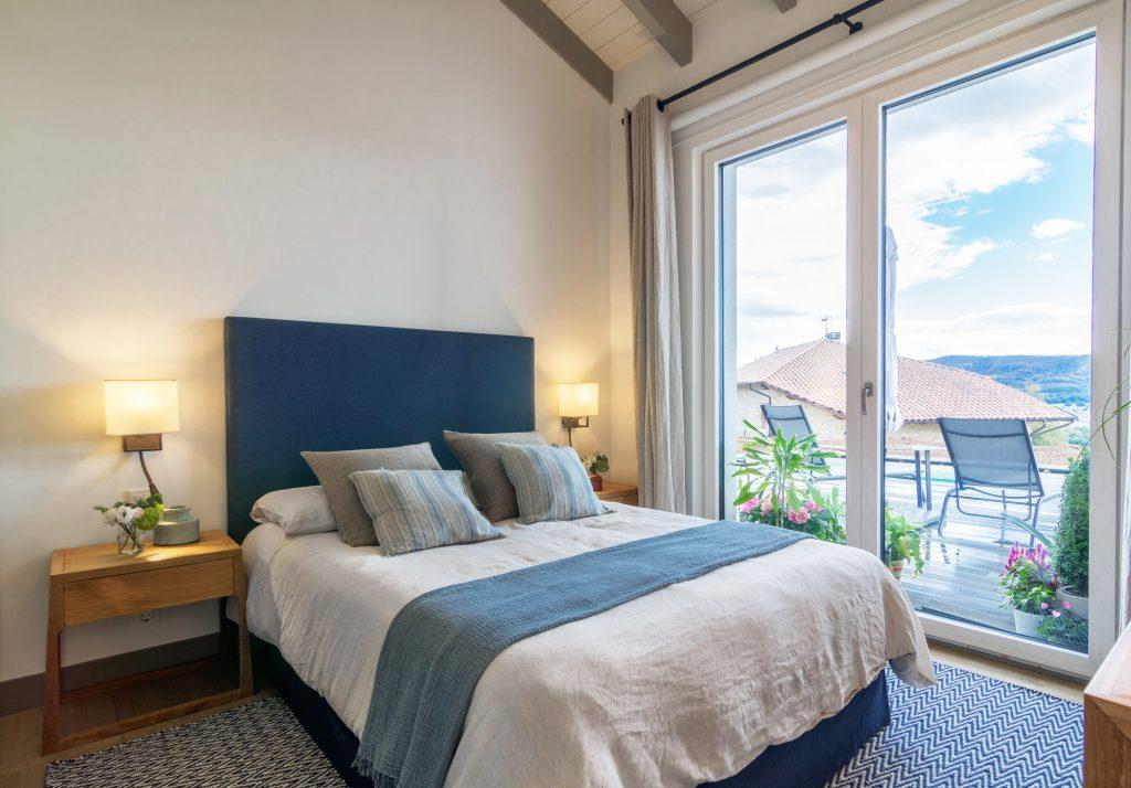 Dormitorio decorado en lino de diferentes azules y muebles auxiliares en madera natural