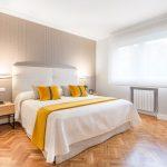Dormitorio empapelado con cabecero de tela decorado por Tribeca Bilbao.