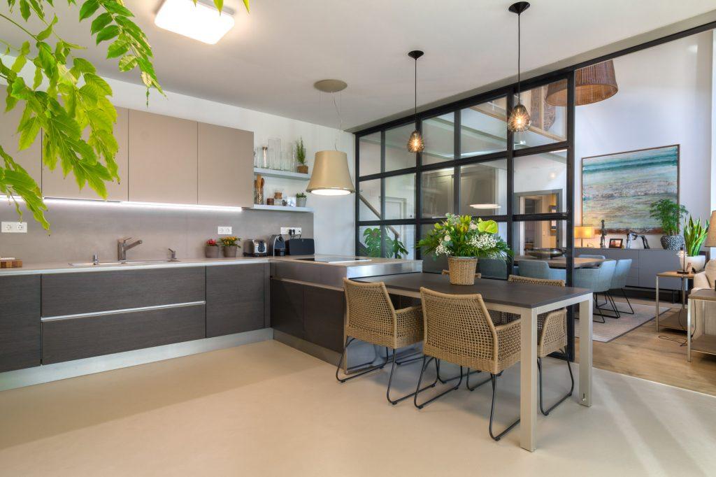 Cocina con mesa extraíble y puerta metálica corredera. Vivienda unifamiliar diseñada por Tribeca.